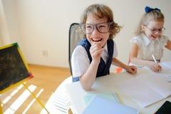 Les petits étudiants ridicules à lunettes, le garçon et la fille, partagent le même bureau photographie stock