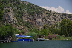 Les petits bateaux aux tombeaux de Lycian s'approchent de Dalyan images stock