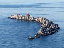 Les petits bateaux de pêche s'approchent de l'île rocheuse avec le phare Image libre de droits