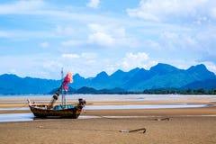 Les petits bateaux de pêche sur le sable échouent pendant la marée basse avec le ciel bleu nuageux Images libres de droits