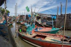 Les petits bateaux de pêche thaïlandais se sont accouplés au village de pêche au jour t Photos stock