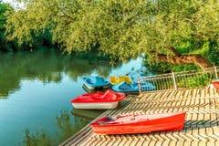Les petits bateaux de voile et de pédale se sont garés par la berge au coucher du soleil d'été Arrosez les attractions et arrosez Image stock