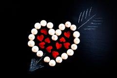 Les petits biscuits se sont étendus sous forme de coeur avec la flèche et le papier il Photo stock