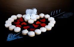 Les petits biscuits se sont étendus sous forme de coeur avec la flèche et le papier il Photographie stock