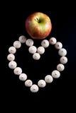 Les petits biscuits se sont étendus sous forme de coeur et pomme mûre sur le noir Photographie stock libre de droits
