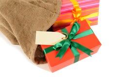 Les petits cadeaux de Noël et la distribution du courrier intérieure de label mettent en sac, le fond blanc Photographie stock