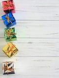 Les petits cadeaux de Noël sur un blanc rustique ont lavé le bois Image stock