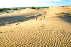 Les petits cerfs-volants pilotent et donnent un coup de pied la boule sur la colline de sable photos libres de droits