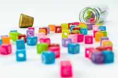 Les petits cubes colorés d'isolement avec des caractères ont dispersé de la fiole sur le fond blanc Photos libres de droits