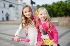 Les petits enfants apprenant à monter des scooters dans une ville se garent la soirée ensoleillée d'été Petites filles mignonnes  Images libres de droits