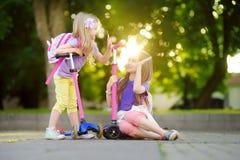Les petits enfants apprenant à monter des scooters dans une ville se garent la soirée ensoleillée d'été Petites filles mignonnes  Image libre de droits