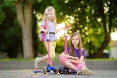 Les petits enfants apprenant à monter des scooters dans une ville se garent la soirée ensoleillée d'été Petites filles mignonnes  Photo stock