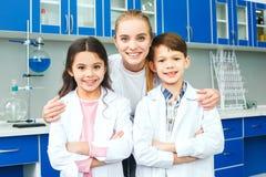 Les petits enfants avec le professeur dans le laboratoire d'école team photos libres de droits