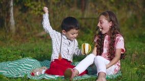Les petits enfants mangent une banane en nature banque de vidéos