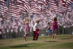 Les petits enfants marchent sous l'affichage des drapeaux des Etats-Unis Images stock