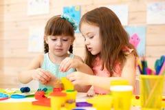 Les petits enfants ont un amusement ainsi que l'argile colorée à la garde Enfants créatifs moulant dans le jardin d'enfants Enfan image libre de droits