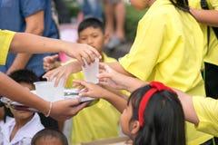 Les petits enfants s'aident avec de l'eau aux amis dans Image libre de droits