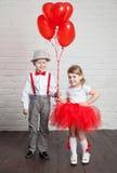 Les petits enfants tenant et prenant le coeur monte en ballon Saint-Valentin et concept d'amour, sur le fond blanc Photo stock