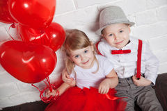 Les petits enfants tenant et prenant le coeur monte en ballon Saint-Valentin et concept d'amour, sur le fond blanc Image libre de droits