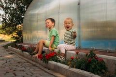 Les petits enfants, une fille et un garçon, s'asseyent sur un chemin près d'un club, nu-pieds, derrière eux une piscine couverte, photos libres de droits