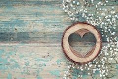 Les petits fleurs blanches et coeur ont découpé en bois sur le vieux grunge p Photos stock