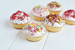 Les petits gâteaux avec de la crème blanche et arrose sur le fond blanc Photographie stock