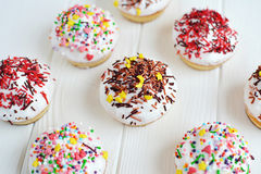 Les petits gâteaux avec de la crème blanche et arrose sur le fond blanc Photo libre de droits