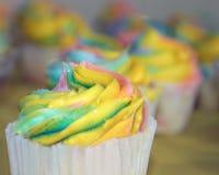 Les petits gâteaux avec le givrage d'arc-en-ciel ont tourbillonné et foyer sur le plan Photo libre de droits