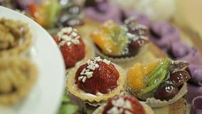 Les petits gâteaux délicieux couvrent la table de mariage Buffert de sucrerie Tir en gros plan banque de vidéos