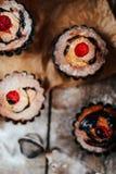 Les petits gâteaux délicieux de chocolat avec des baies wodeen dessus la table, v supérieur Photo stock
