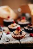 Les petits gâteaux délicieux de chocolat avec des baies wodeen dessus la table, v supérieur Image stock
