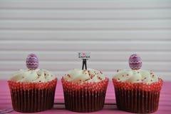 Les petits gâteaux délicieux de chocolat ont complété avec une figurine miniature de personne tenant un signe indiquant l'amour P Image libre de droits