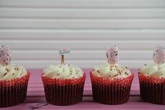 Les petits gâteaux délicieux ont complété avec une figurine miniature de personne tenant un signe indiquant l'amour Pâques d'I Image libre de droits