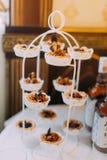 Les petits gâteaux délicieux placés sur le dessert blanc se tiennent Photographie stock libre de droits