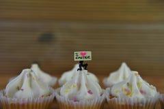 Les petits gâteaux d'Eastertime avec une figurine miniature de personne tenant un signe indiquant I aiment Pâques Photos libres de droits