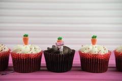 Les petits gâteaux de chocolat de temps de Pâques ont complété avec des carottes glacées et une figurine miniature de personne te Images stock