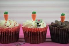 Les petits gâteaux de chocolat de temps de Pâques ont complété avec des carottes glacées et une figurine miniature de personne te Photo libre de droits