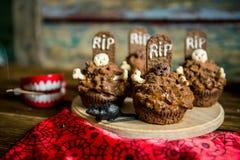 Les petits gâteaux de Halloween avec la pierre tombale durcissent le haut de forme et le mirent sur une vieille table en bois Photographie stock libre de droits
