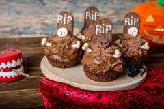 Les petits gâteaux de Halloween avec la pierre tombale durcissent le haut de forme et le mirent sur une vieille table en bois Image stock
