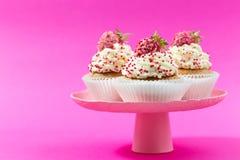 Les petits gâteaux de vanille ont décoré des fraises sur un backgground rose Photo stock