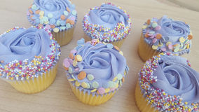 Les petits gâteaux givrés par pourpre avec arrose Photos stock