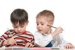 Les petits garçons écrivent au bureau Images stock