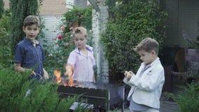 Les petits garçons joue avec le feu dans le gril de barbecue clips vidéos
