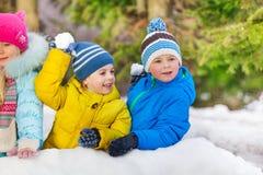 Les petits garçons mignons jouent le combat de boule de neige en parc Photo libre de droits