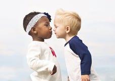 Les petits gosses divers embrassent d'abord Photographie stock