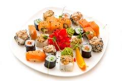 Les petits pains assortis de fruits de mer ont admirablement présenté sur un plateau sur un fond blanc photos stock