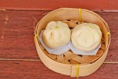 Les petits pains cuits à la vapeur de porc ou le petit pain chinois dans le panier en bambou ont mis dessus une texture en bois Image stock
