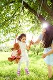 Les petits pains de maman sur un ` s d'enfant balancent en parc pendant l'été Photographie stock libre de droits