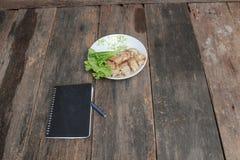 les petits pains de ressort versent la sauce dans le plat avec le carnet noir et le légume frais sur la table en bois image stock