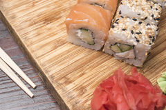 Les petits pains de sushi avec les saumons, le sésame noir et blanc et le gingembre se trouvent sur un conseil en bois léger Photographie stock